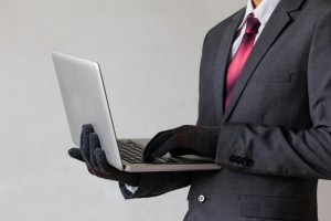 Business man wearing gloves and using computer - fraud concept