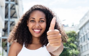 Young caribbean woman with curly hair in city showing thumb