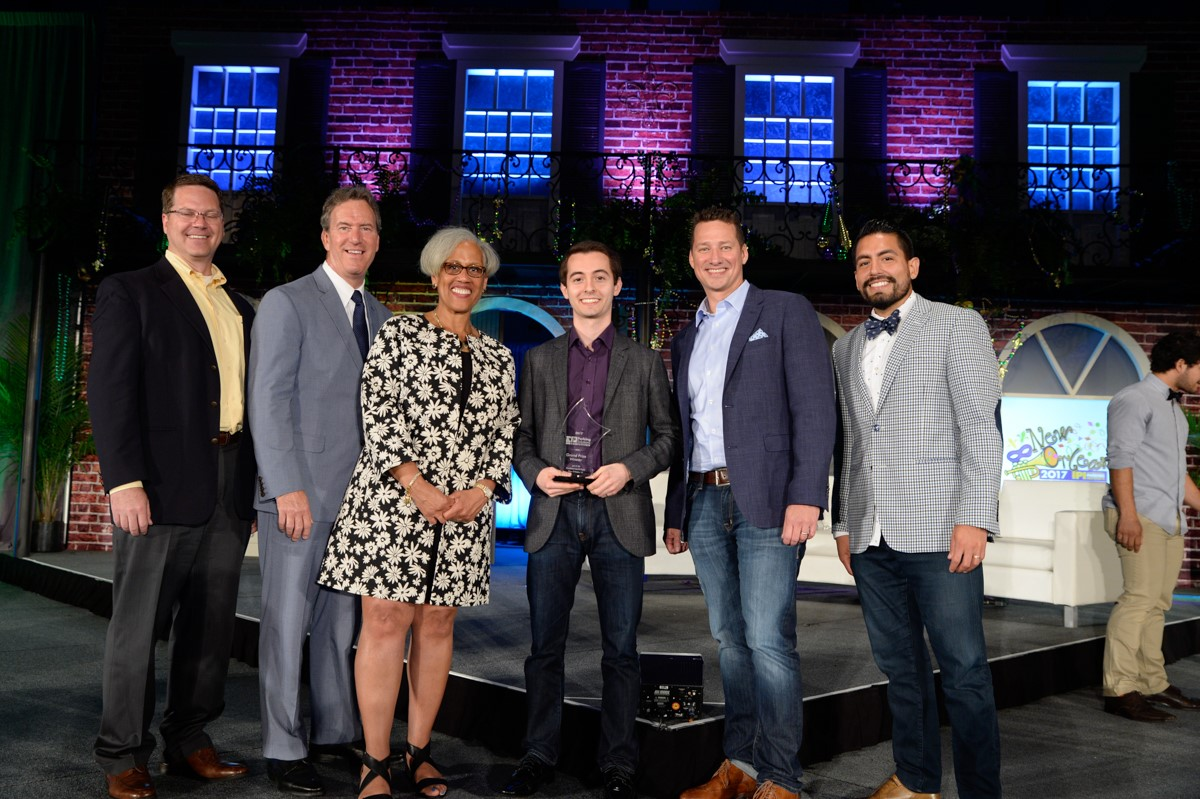 Adam pictured onstage with judges and IPI CEO, Shawn Conrad.