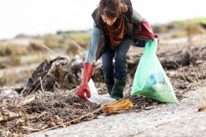 Woman bending over to pick up trash