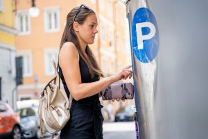 Woman paying for parking at multi-space meter