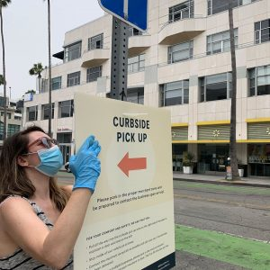 "A woman in a medical mask and gloves hangs a ""curbside pickup"" sign."