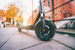 A kick scooter on a city sidewalk