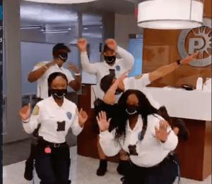 Parking officers dance wearing masks.