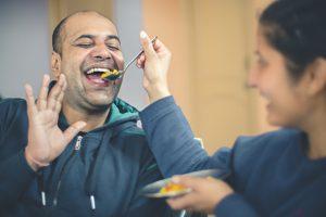Woman feeding man with a spoon.
