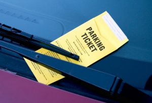 yellow parking ticket under a car windshield wiper