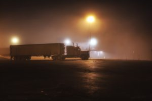 tractor trailer parked in empty, dark parking  lot
