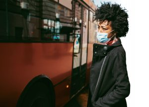 woman wearing medical mask boarding a bus.