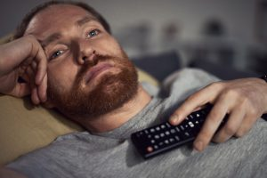 Portrait of bearded adult man watching TV at night while lying on couh in dark room and switching channels