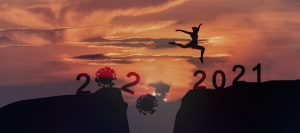 Woman leaping across ravine, one side says 2020 and the other side says 2021