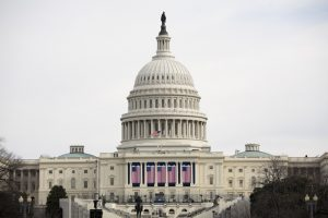 U.S. Capitol building with flags draped across the front and an inauguration stage on the steps.
