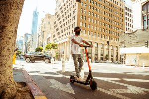 Man wearing mask riding Spin scooter on a city street.