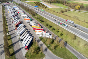 Aerial view of a multiple lane highway and a large truck stop with long rows of parked semi trucks.
