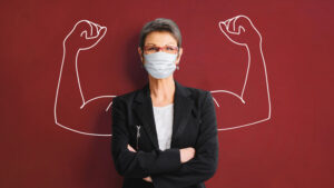 woman in medical mask with strong arms drawn on the wall behind her