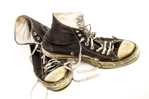 Close-up teenager's retro style black and white tennis shoes, tattered, ripped, dirty, isolated on white background