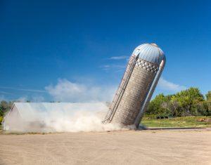 Farm silo falling down into a field