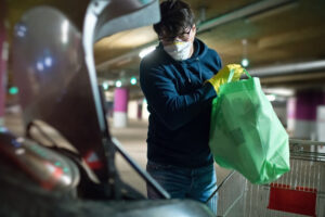 Man in mask and rubber gloves putting products in car after shopping