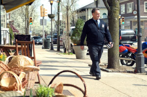 Parking ticket officer walks over Germantown Avenue in the shopping district of Chestnut Hill, Philadelphia.
