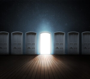 Hallway of dark doors, one opened to light