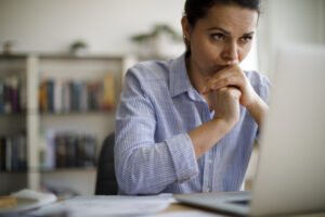 Worried woman looking at computer screen