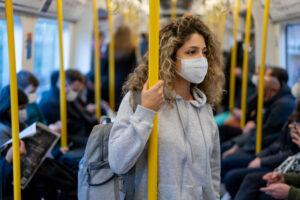 woman riding commuter train wearing a face mask
