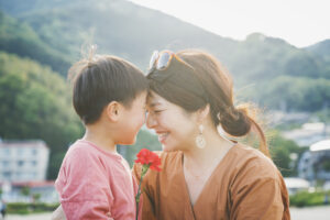 Boy handing mother a carnation flower