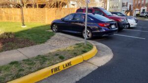 An ADA sidwalk cut is positioned at the side of a parking space.