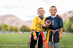 Two boys in football uniforms posing for the camera