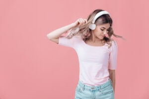 woman in pink t-shirt and white headphones listens to music and smiling with closed eyes on pink background