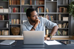 Black businessman sitting at workplace thinking over problem solution