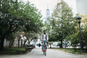 A young African American man explores New York City with his fixed gear bicycle. One World Trade Center visible in skyline behind him.
