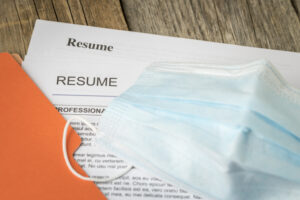 Stock photograph of job resume inside orange folder with mask.