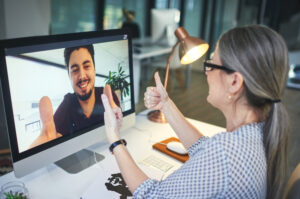 Shot of a young man showing thumbs up during an online meeting with a colleague