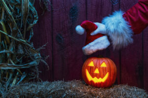 Santa's gloved hand placing a Santa Hat on a carved glowing happy Jack O' Lantern looking at the camera sitting on a bale of straw with dried corn stalks and a weather red barn wall in the background at night under a blue moon light.