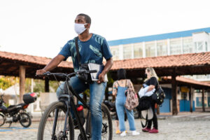 College student wearing a mask and biking on campus.
