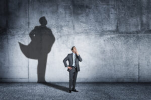 A man strikes a contemplative pose as his shadow that is cast on the wall behind him shows him in a confident stance and wearing a cape.