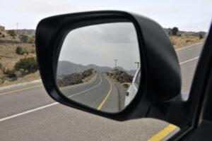 car rear view mirror reflecting a road